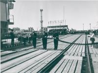 Открытие паромной переправы в г. Холмске. На переднем плане изображены три мужчины в момент перерезания ленты. По сторонам (слева и справа) стоят пионеры, отдающие салют. На заднем плане трибуна с выступающими и колонны людей, участвующих в митинге. Люди держат флаги, транспаранты. Трибуна украшена флагами.