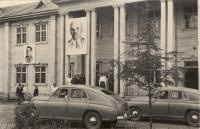 Анивский Дом Культуры, выстроенный народной стройкой. На снимке изображен фрагмент фасада здания с колоннами у подъезда. На подъезде стоит группа людей. Перед зданием стоят две машины.