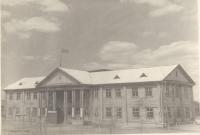 Анивский Дом Культуры. На снимке изображен фасад двухэтажного здания с колоннами у парадного подъезда; по центру, между лестницами построена трибуна. На крыше реет флаг.