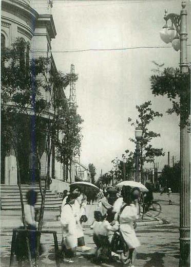 Прогулка жителей города рядом со зданием почты.