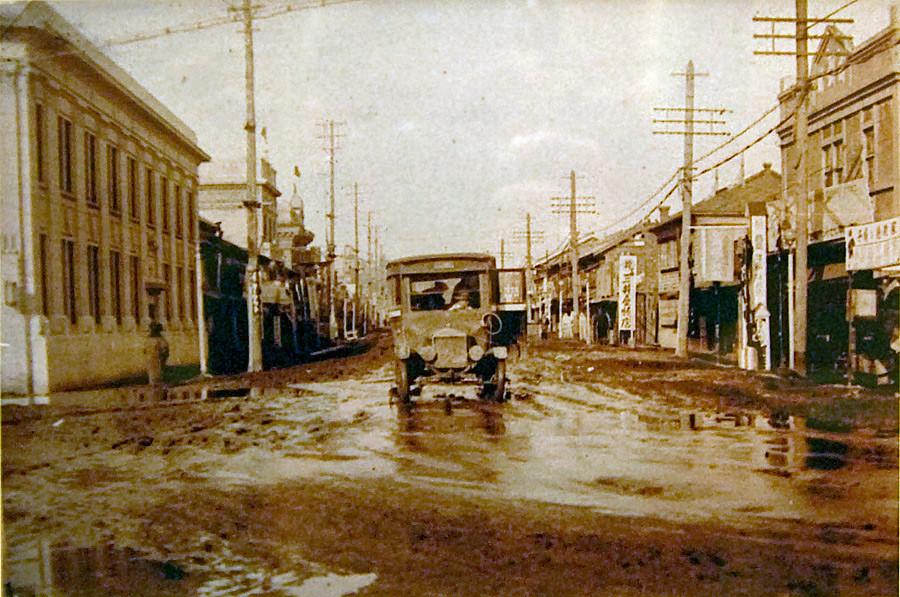 Вид на улицу Советскую. Слева отделение банка. Автомобиль на дороге 'Mitsubishi Model A'. Год съемки приблизителен.