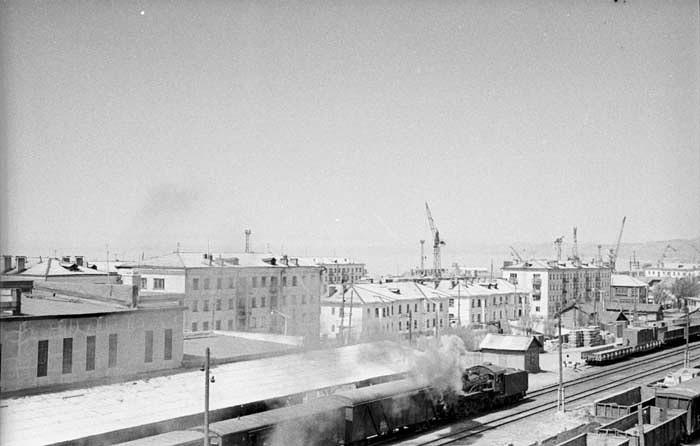 Поезд у перрона железнодорожного вокзала, вдали виднеются дома по улице Советской. г. Холмск