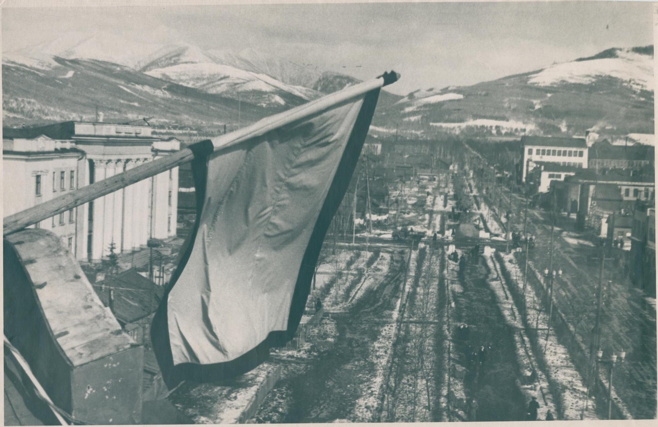 Панорама части города Южно-Сахалинска (вид сверху на улицу Сталина). На переднем плане с левой стороны – траурный флаг, прикрепленный к крыше здания.