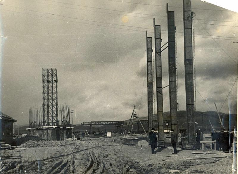 Строительство Сахалинской ГРЭС. Размытая грязью дорога (в центре), строительные материалы и сооружения (слева), возле вертикально расположенных металло-бетонных балок стоят двое мучин. Мужчина слева изображен в рост, поворот в три четверти влево, одетый в тёмное пальто, брюки, на голове шляпа. Мужчина справа изображён в рост, повёрнут лицом к мужчине, который стоит слева, одетый в рабочую одежду темного цвета: фуфайку, штаны, шапку.