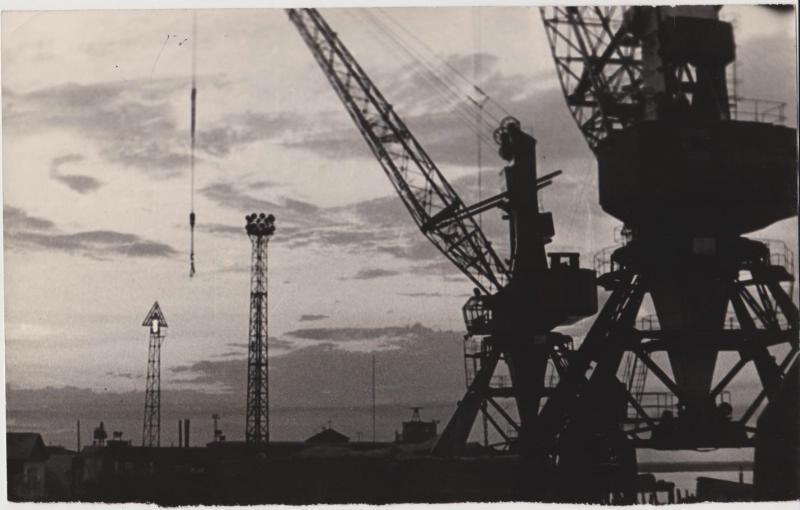 На фоне вечернего неба, справа стоят два крана 'Ганц' на территории Поронайского морского торгового порта, на заднем плане - две вышки и постройки.
