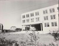 Средняя школа № 7. Снимок сделан со стороны улицы Победы. Школьный двор с молоденькими деревцами, крупным планом - часть здания с порталом с колоннами. На заднем плане слева - многоэтажные жилые дома поселка бумажников.
