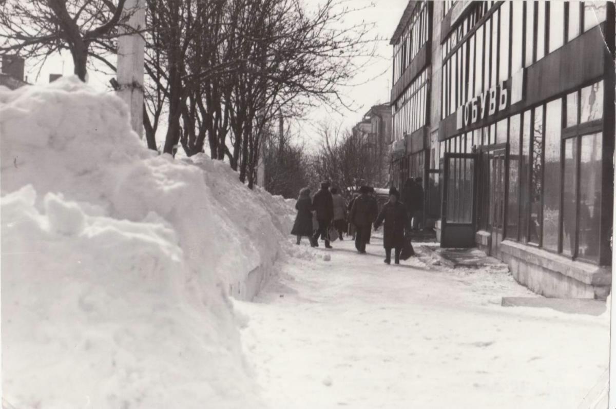 Вид заснеженного тротуара улицы Советской и боковой вид фасада магазина 'ОБУВЬ' по адресу ул. Советская, дом 23