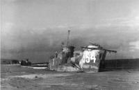 Выгоревший корпус cоветского десантного корабля американского производства ДС-9 (LCI-554) на пляже,  где произошла высадка десанта.  В бою погиб почти весь экипаж десантного судна во главе с командиром — лейтенантом  В.П. Гурьевым.
